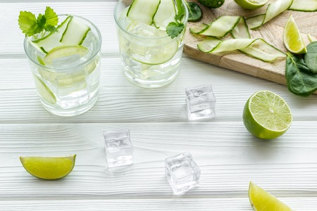 Summer cocktails for freshness with lime, cucumber and ice on wooden table background