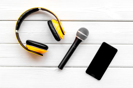 Record studio set. Blogger, journalist or musician work space with microphone, mobile telephone and headphones on white wooden background top view mockup Stock Photo