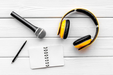 Microphone, headphones, notebook for blogger, journalist or musician work on white wooden office desk background top view mockup