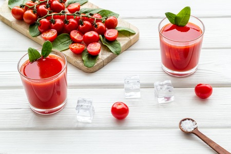 Fresh healthy fruit drink with tomato and ice on white table background