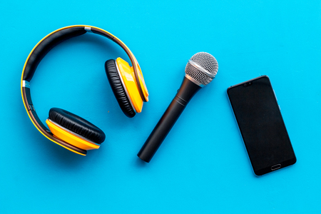 Microphone, headphones, mobile phone for blogger, journalist or musician work on blue office desk background top view mockup