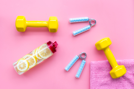 Workout with bars, bottle of water and wrist builder on pink background top view mockup 写真素材