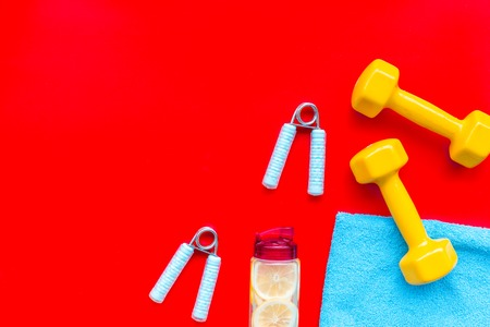 Workout with bars, bottle of water and wrist builder on red background top view mockup