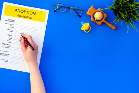Family and adoption child concept with application, dummy, toy, glasses on blue table background top view mockup
