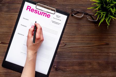 Concepto de empleo con currículum vitae o CV sobre fondo de escritorio de madera con bolígrafo, espacio de vista superior de gafas para texto