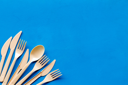 Ecology. Plastic utilization and the Earth protection concept with flatware on blue background top view mock up