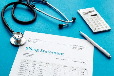 Medical treatment bill, calculator and phonendoscope on blue desk background Stock Photo