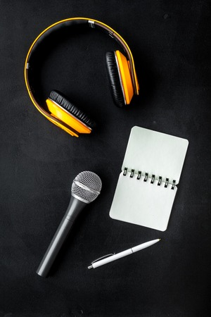 Record studio set. Blogger, journalist or musician work space with microphone, notebook and headphones on black background top view mockup Stock Photo