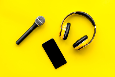 Microphone, headphones, mobile phone for blogger, journalist or musician work on yellow office desk background top view mockup Stock Photo