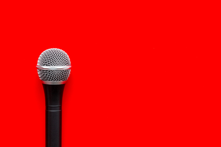 Microphone for blogger, journalist or musician work on red office desk background top view mock-up Stock Photo