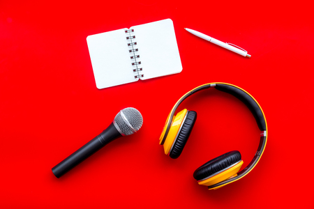 Microphone, headphones, notebook for blogger, journalist or musician work on red office desk background top view mockup
