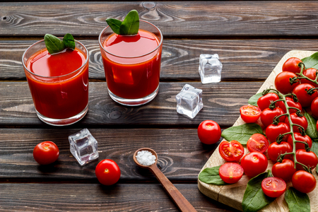 Summer cocktails for freshness with red tomato and ice on wooden table background