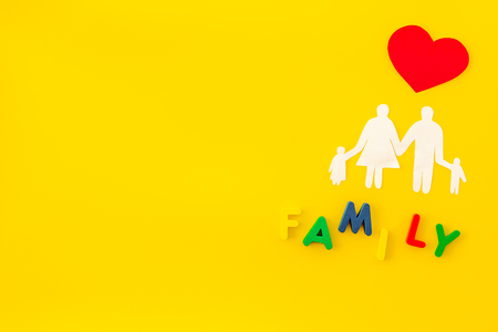 Family copy for adoption child concept on yellow table background top view mockup
