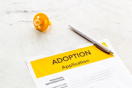 Children care with adoption application and dummy on white office table background