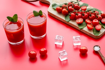 Summer cocktails for freshness with red tomato and ice on red table background