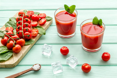 Summer cocktails for freshness with red tomato and ice on mint green wooden table background