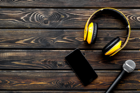 Microphone, headphones, mobile phone for blogger, journalist or musician work on wooden office desk background top view mockup Stock Photo