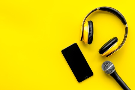 Record studio set. Blogger, journalist or musician work space with microphone, mobile telephone and headphones on yellow background top view mockup Stock Photo