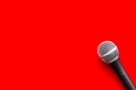 Record studio set. Blogger, journalist or musician work space with microphone on red background top view space for text