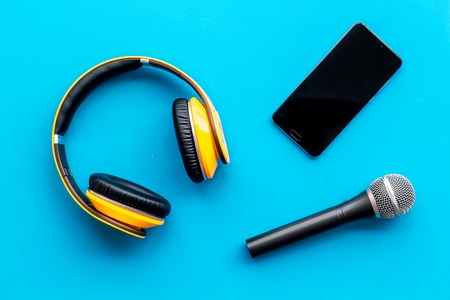Podcast record with mobile phone, microphone and headphones on blue office desk background top view space for text Stock Photo