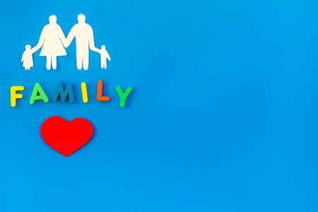 Paper figure for adoption concept with family copy on blue background top view space for text