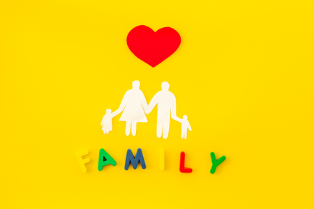 Family word and figure for adopt child concept on yellow table background top view