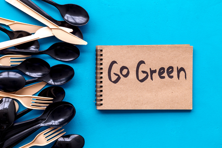 Go green. Planet protection. Eco concept and injunction on the use of plastic flatware on blue background top view.