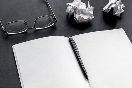 Work desk of writer with notebook, glasses, pen on black desk background mock up