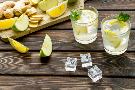 Cold water with ice, orange and apple slices for summer healthy drink on wooden table background