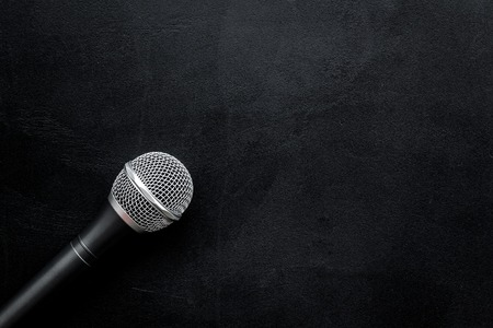 Microphone for blogger, journalist or musician work on black office desk background top view mock-up
