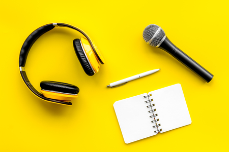 Record studio set. Blogger, journalist or musician work space with microphone, notebook and headphones on yellow background top view mockup Stock Photo