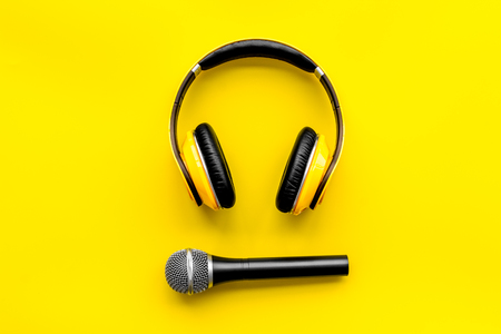 Record studio set. Blogger, journalist or musician work space with microphone and headphones on yellow background top view