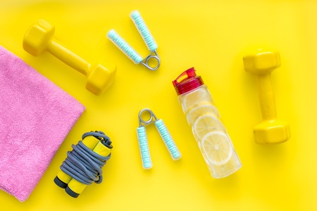 Workout with bars, bottle of water and wrist builder on yellow background top view 写真素材