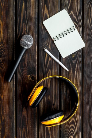 Record studio set. Blogger, journalist or musician work space with microphone, notebook and headphones on wooden background top view mockup