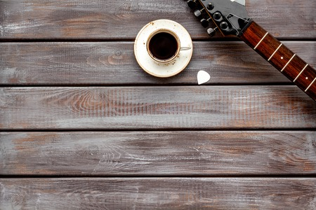 Musician work place with guitar and cup of black coffee on wooden background top view mock up.