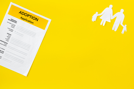 Family and adoption child concept with application on yellow table background top view mockup