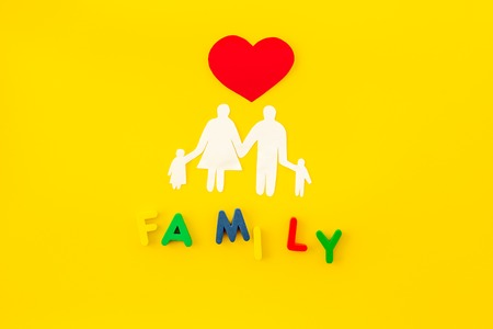 Family copy for adoption child concept on yellow table background top view