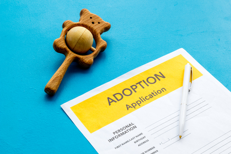 Children care with adoption application and toy on blue office table background