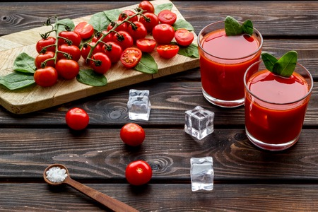 Healthy drinks with tomato and ice for summer freshness on wooden background