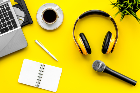 Microphone, headphones, notebook and laptop for blogger, journalist or musician work on yellow office desk background top view mock up Stock Photo