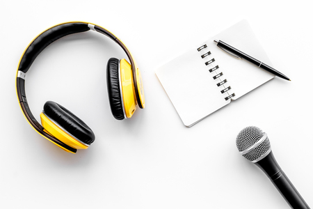 Podcast record with notebook, microphone and headphones on white office desk background top view space for text