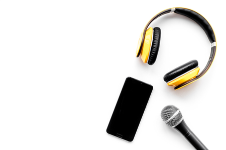 Microphone, headphones, mobile phone for blogger, journalist or musician work on white office desk background top view mockup