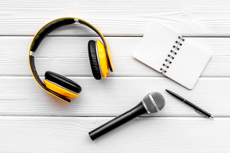 Blogger, journalist or musician office desk with notebook, microphone and headphones on wooden studio background top view copyspace