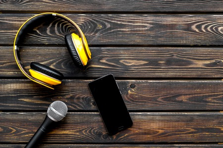 blogger, journalist or musician office desk with mobile phone, microphone and headphones on wooden studio desk background top view copyspace