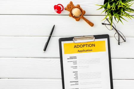 Adoption application, glasses and dummy on white wooden table background top view Stock Photo