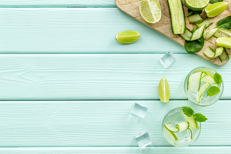 Summer cocktails for freshness with lime and cucumber and ice on mint green table background top view mockup