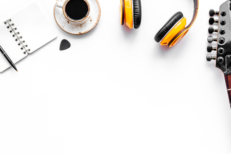 Professional dj instruments on workdesk with headphones, guitar, notebook and coffee on white background top view mockup