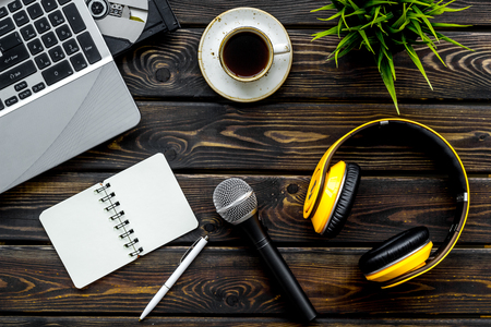 Blogger, journalist or musician office desk with computer keyboard, notebook, microphone and headphones on wooden studio desk background top view copyspace