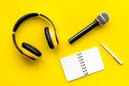 Microphone, headphones, notebook for blogger, journalist or musician work on yellow office desk background top view mockup Stock Photo - 120027899