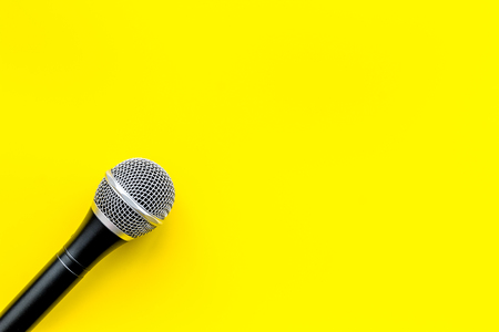 Microphone for blogger, journalist or musician work on yellow office desk background top view mock-up